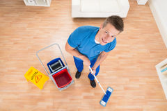 Worker Mopping Wooden Floor Stock Images