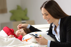 Worker mother working while her toddler sleeps stock photo