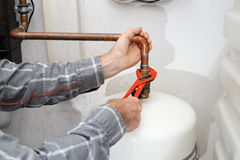 Worker is mounting a heating Stock Image