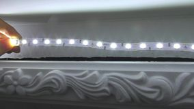 Worker mounting new LED ceiling strip lamp stock video footage