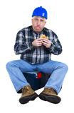 Worker with a mouthful of hamburger. On white background Royalty Free Stock Photos