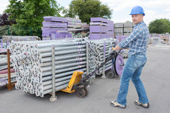 Worker moving pallet scaffold poles Royalty Free Stock Images