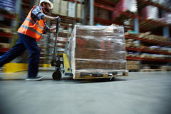 Worker Moving Retail Merchandise in Large warehouse. Blurred motion shot of warehouse worker wearing hardhat and reflective jacket pushing moving cart with boxes Royalty Free Stock Image