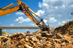 Worker moving rocks with excavator on construction site Stock Photography