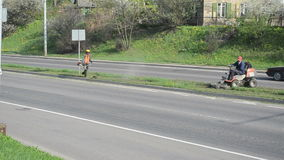 Worker mower trimmer car. Workers cut lawn grass with mower trimmer between street road lines and cars go arround circa May 2013 in Vilnius, Lithuania. City stock video footage