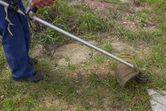 Worker mowing the grass with gas string trimmer Stock Photos