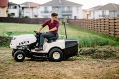 Worker mowing lawn and cutting grass using powerful mower. Professional worker mowing lawn and cutting grass using powerful mower Royalty Free Stock Image