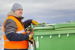 Worker near the garbage containers in winter Royalty Free Stock Images