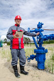 Worker near well head valve Royalty Free Stock Images