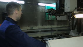 Worker next to machine selects a drill via control panel. stock video footage