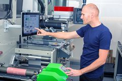 Worker next to the printing machine inputs the data by pressing the touch screen. stock image
