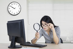 Worker observe computer in office. Female worker observes a computer with a magnifying glass in the office Royalty Free Stock Image