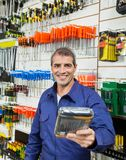 Worker Offering Packed Product In Hardware Store Royalty Free Stock Photo