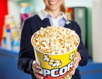 Worker Offering Popcorn Bucket At Cinema Stock Photography