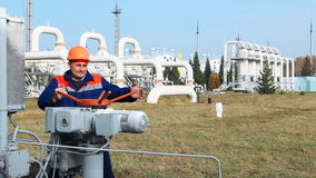 Worker Opens Recirculation Valve. On compressor station of main gas pipeline stock footage