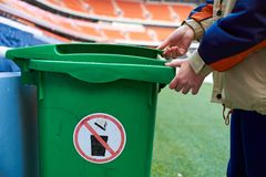 Worker opens trash can. Stadium worker opens trash can royalty free stock photos