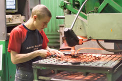 Worker operates computerized metalworking machine Royalty Free Stock Image