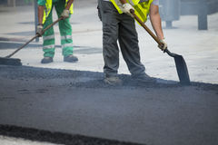 Worker operating asphalt paver machine Stock Images