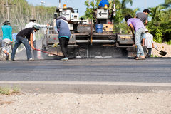 Worker operating asphalt paver machine during road construction. And repairing works focus on asphalt road Stock Photos