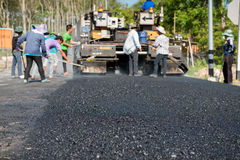 Worker operating asphalt paver machine during road construction. And repairing works focus on asphalt road Royalty Free Stock Photos