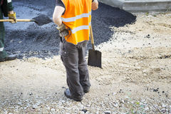 Worker operating asphalt paver machine during road construction and repairing works. Workers smoothing out asphalt pavement at the end of the run for a new road Royalty Free Stock Photos