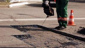 Worker operating asphalt repairing works stock video footage