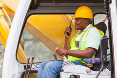 Worker operating bulldozer. African industrial worker operating bulldozer while talking on walkie-talkie Royalty Free Stock Photography