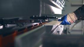 Worker operating CNC hydraulic press brake. Bending sheet of metal. Close-up.