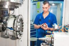 Worker operating CNC machine center Stock Image