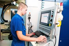 Worker operating CNC machine center Stock Image