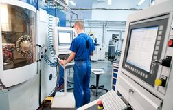 Worker operating CNC machine center stock photo
