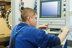 Worker operating CNC machine center Royalty Free Stock Photo