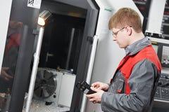 Worker operating CNC machine center Stock Photo