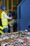 Worker Operating Conveyor Belt In Recycling Factory. Side view of young worker operating conveyor belt in recycling factory Royalty Free Stock Photo