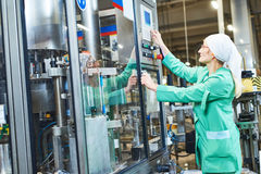 Worker operating conveyor or labeling machine at factory. Factory worker operating labeling machine or conveyer in food and drink production industry Stock Image