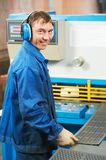 Worker operating guillotine shears. Worker at workshop operating guillotine shears machine Stock Photography