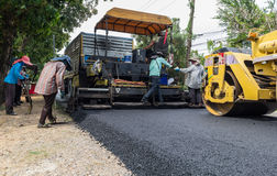 Worker operating industrial asphalt paver machine during highway construction Royalty Free Stock Photography
