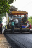 Worker operating industrial asphalt paver machine during highway construction Royalty Free Stock Image