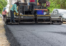 Worker operating industrial asphalt paver machine during highway construction Stock Images