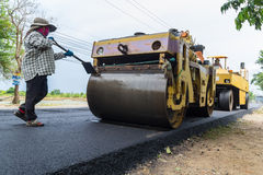 Worker operating industrial asphalt paver machine during highway construction Royalty Free Stock Images