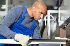 Worker operating machine for bending sheet metal. Worker operating a machine for bending sheet metal Stock Images