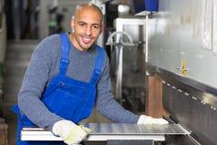 Worker operating machine for bending sheet metal Royalty Free Stock Photos
