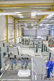 Worker operating machinery in factory that manufactures aluminium light fittings Royalty Free Stock Photo