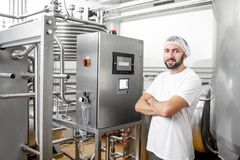 Worker at the cheese manufacturing. Worker operating pasteurizer using the control panel at the cheese or milk manufacturing stock photo
