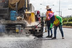 Worker operating the process of building new asphalt road on the. Outdoor working : Worker operating the process of building new asphalt road on the new road Stock Photo