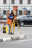Worker is operationg a theodolite. Land surveyor man is operating a theodolite on the small street in Moscow Royalty Free Stock Photos