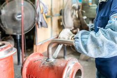 Worker or operator cleaning welding seam remove by knock with hammer and chisel at factory.  stock photography