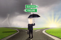 Worker with options to success or failure. Entrepreneur with a carton head and holds an umbrella, standing on the road while looking at two signpost to success Stock Photography