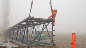 Worker in Orange Coveralls Climbing Down the Scaffold stock footage