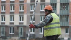 Worker in orange hard hat smoking at building site, holding long metal ruler stock video